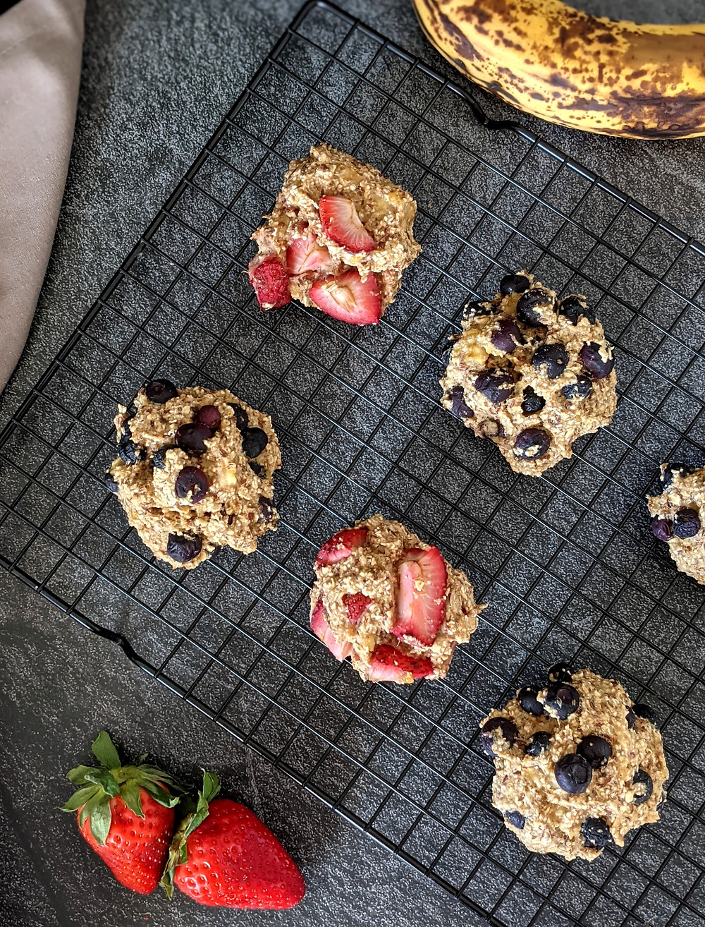 Muffin tops made with blueberries and strawberries on a cooling rack,