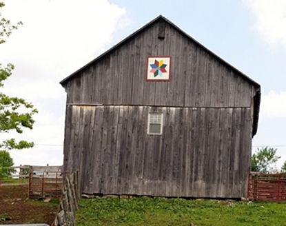 star pattern barn quilt on a gray barn