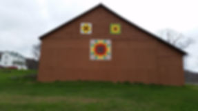 big barn with three barn quilts of sunflowers