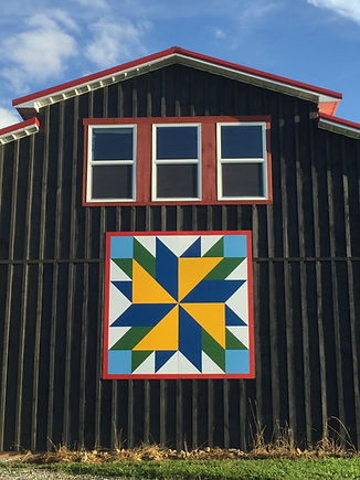 large 8' barn quilt on a black barn. Low Lands to High Country