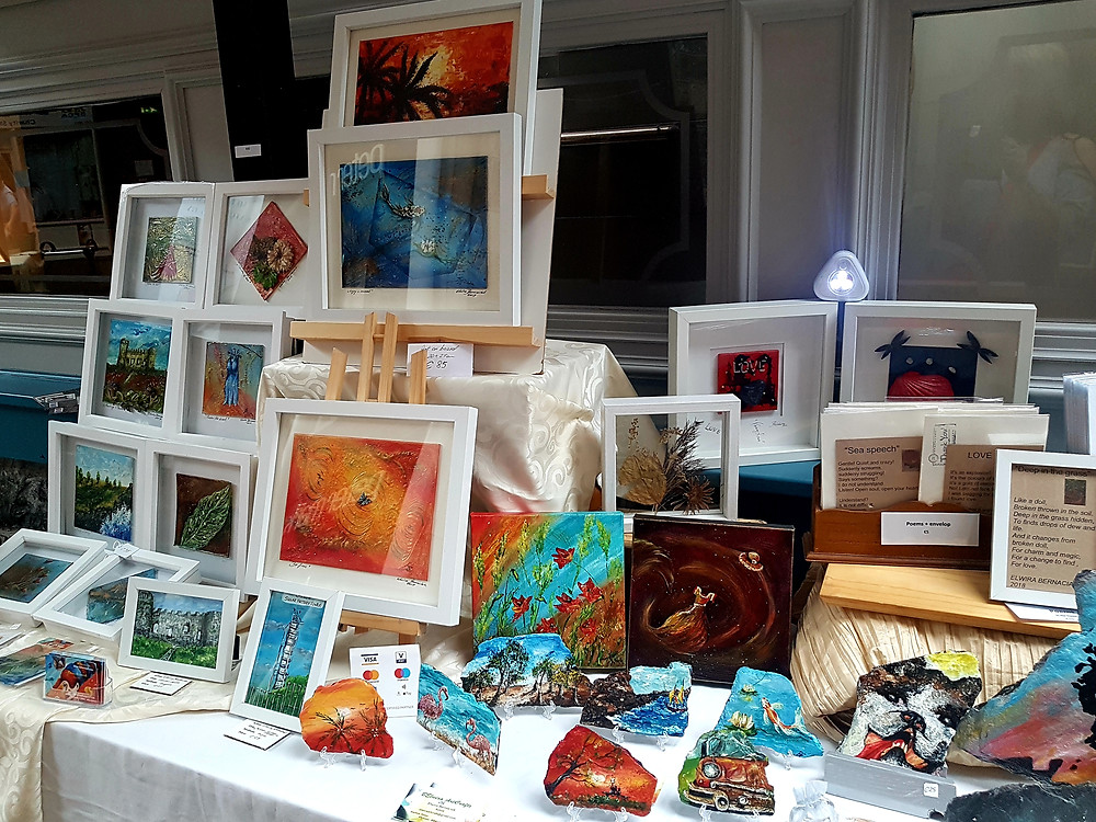A display of small, handmade acrylic arts on canvas and stones