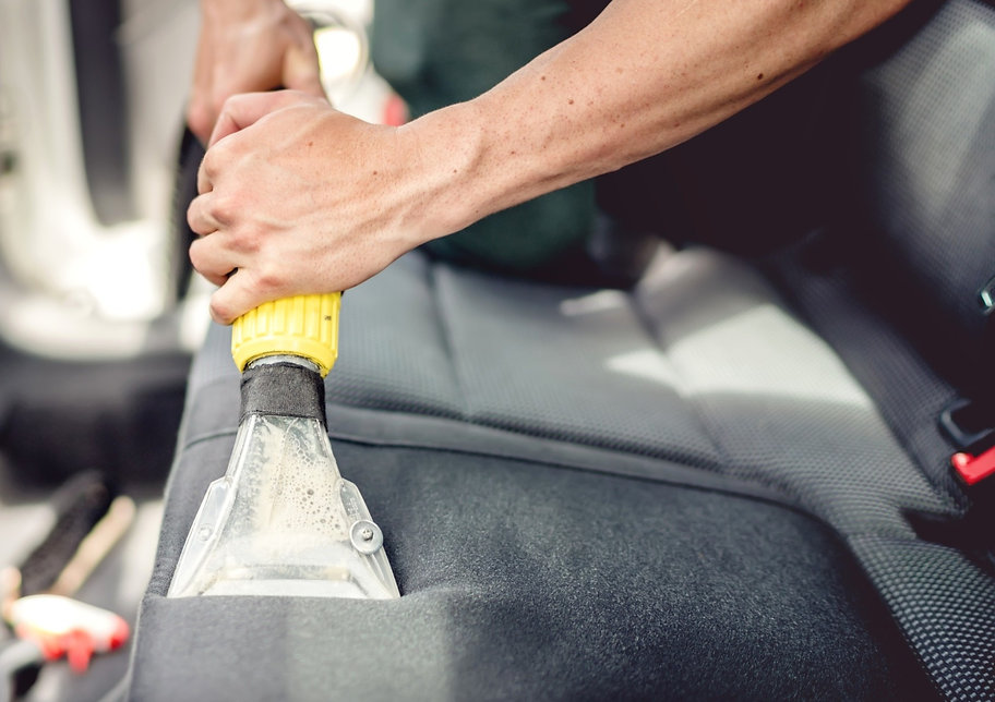 Auto detailer extracting dirt from seats
