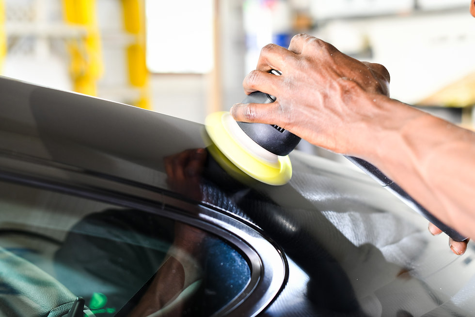 Professional auto detailer using dual action polisher to perform paint correction
