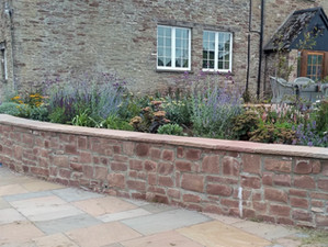 Garden wall, paving and raised beds