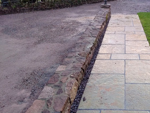 Tumbled limestone paving, turfing and dwarf wall