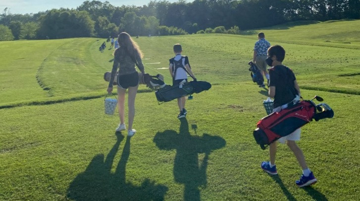 Juniors walking with golfbags.jpg