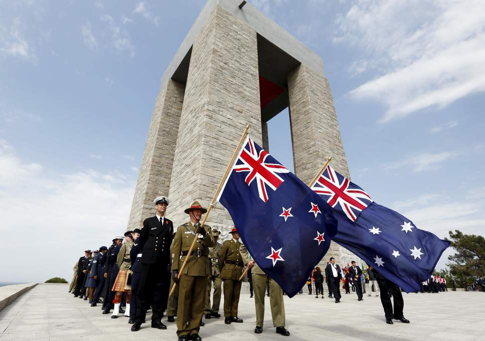 Australian and New Zealand servicemen in a remembrance service at an ANZAC memorial