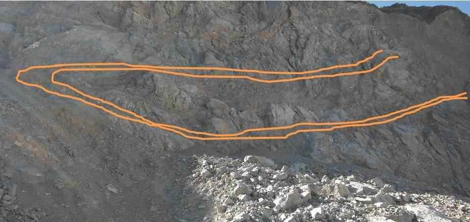 Pliegue sinclinal recumbente asimétrico con plano axial buzante al este. En color naranja se destaca nivel guía de metalutitas grises con migración de material hacia la zona de charnela.