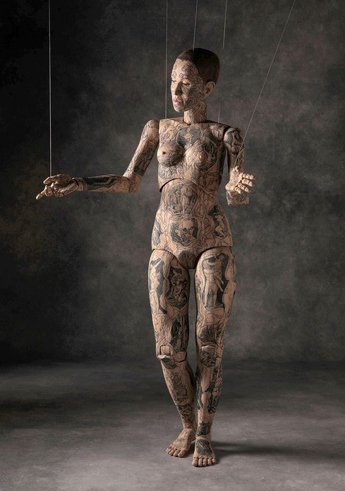 life size wooden sculpture of a female doll like figure