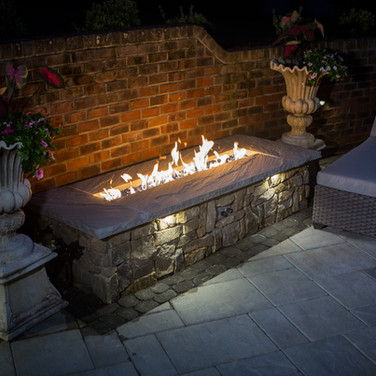 Disappearing waterfall, outdoor firepit, covered patio with pavers and landscape lighting