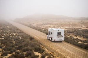 A motorhome drives along a gravel road.