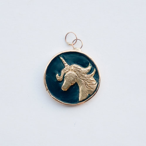 A unicorn medallion charm set in 14K yellow gold.