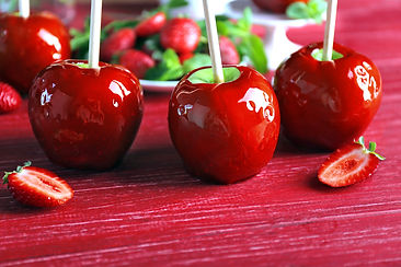 Candy apples with strawberry on red wood