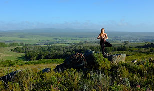 Yoga on the rocks - tree pose with view of the valley