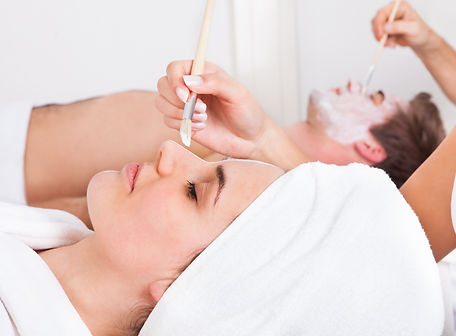 Therapist Applying Facial Mask To Young Couple At Beauty Salon.jpg