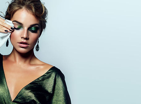 beautiful young girl with a bright make-up and in a shiny green dress striatet makeup from