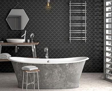 Bathroom showing a retro bath tub and black scale retro wall tiles, ladder towel warmer, bathroom cabinet