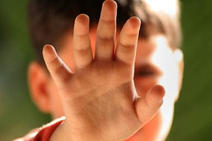 child with hand blocking face