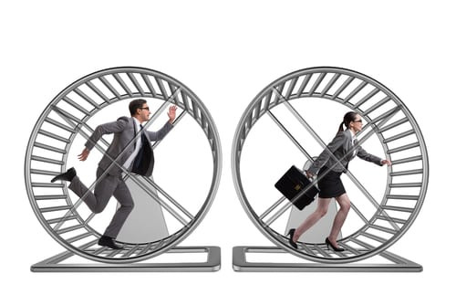 Two business people running in a hamster wheel
