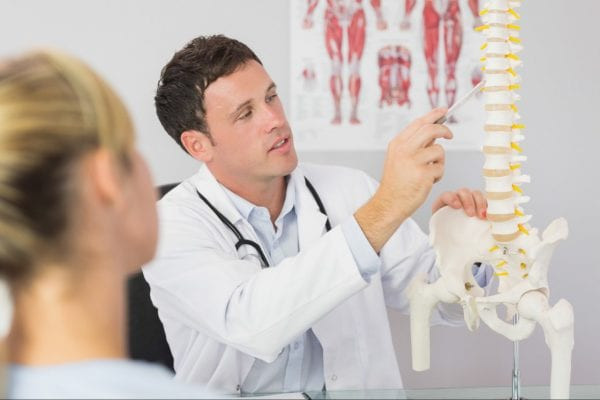 Chiropractor pointing to spine