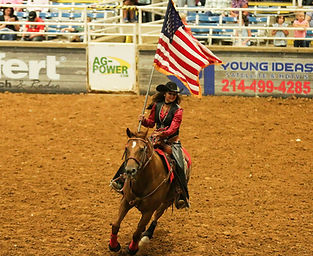 girl riding horse carrying American flag