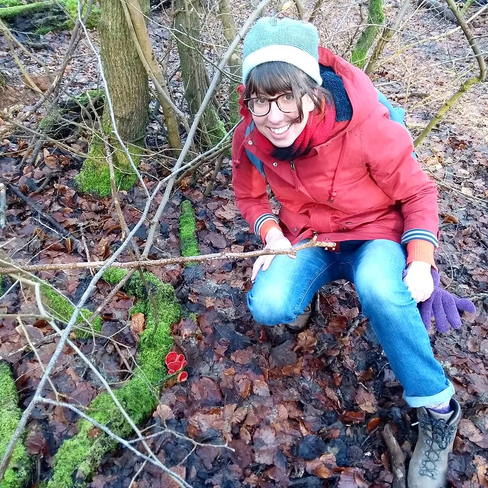 Emily is crouched in woodland next to a cluster of small red mushrooms. She is in a hat and coat and smiling at the camera.