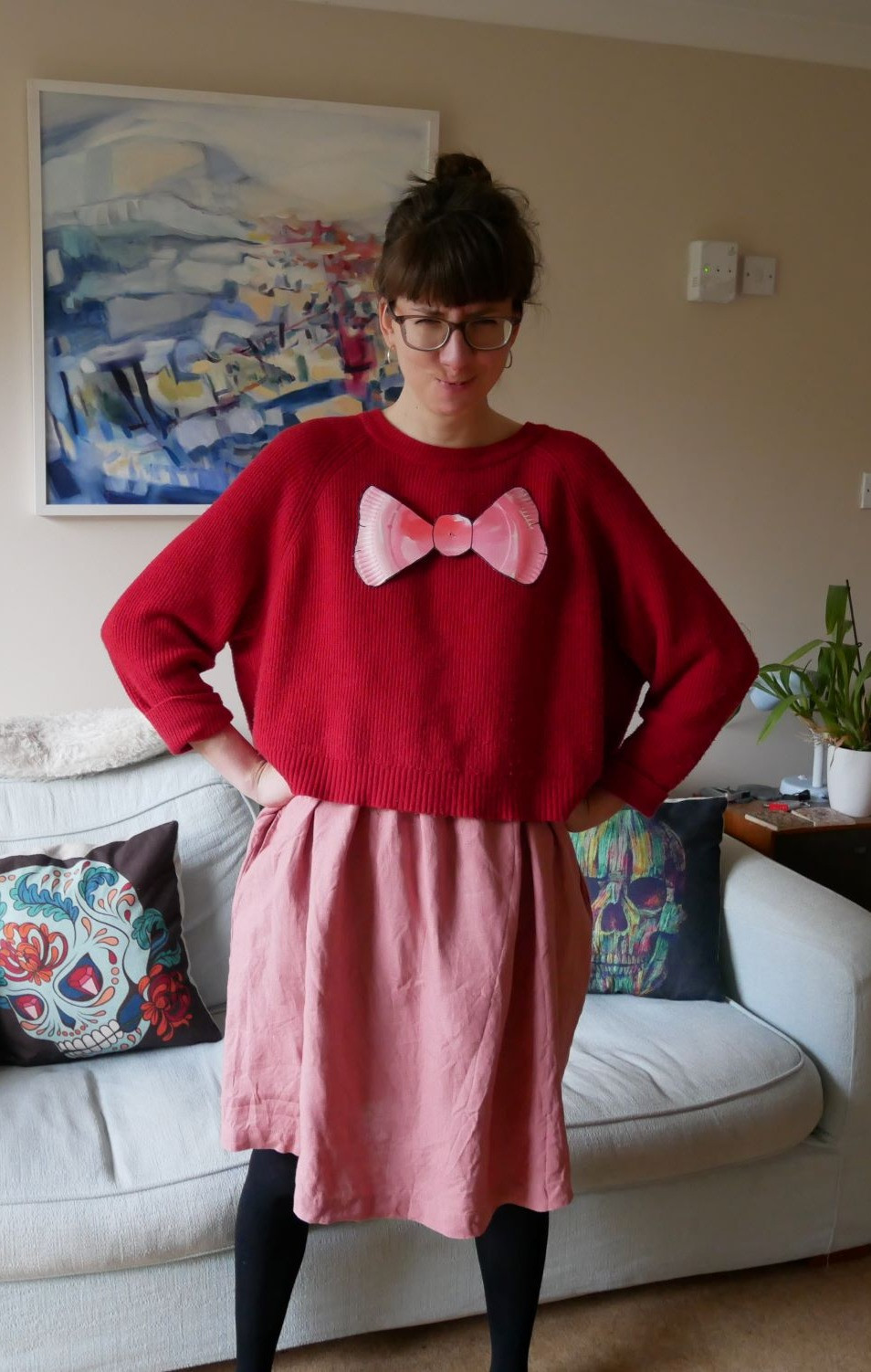 A woman stands with her hands on her hips. She is wearing a red jumper over a pink dress and black tights. She has a big pink bow made out of paper stuck onto her jumper. She is frowning at the camera.