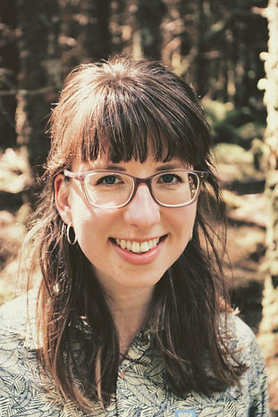 A smiling white woman with glasses and brown hair. Trees are in the background.