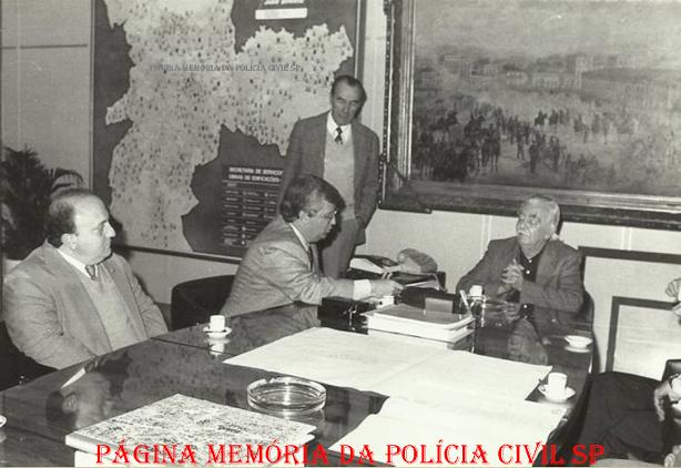 """Delegado de Polícia Cyro Vidal Soares da Silva """"in memorian"""", recebido pelo então Prefeito SP Jânio Quadros, em 1.986, que lhe entrega um relatório em seu gabinete, estando à esquerda sentado, Francisco de Migueli. Em pé o escrivão Julio, na época trabalhando na DEAT. O assunto era o evento Feira do Automovel no Anhembi, onde o Detran colocou um posto de vistoria à disposição dos frequentadores, autorizado pelo então Prefeito visando o comercio de veículos sem intermediários."""