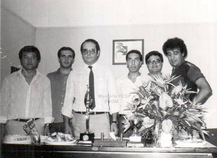 """A frente, em cima da mesa o troféu da Campeã do mês: a Equipe """"F"""" da Divisão de Homicidios do DEIC, em 1.984, da esquerda para a direita, Escrivães Hono, Edison Lahoz (hoje Delegado de Policia), Delegado de Polícia Marco Antônio Desgualdo (ex-DGP), Gabi, ? e Osvaldinho."""