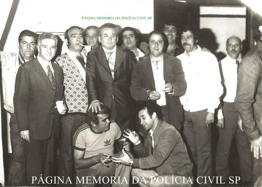 """Investigadores de Polícia da DIG- DEIC, em 1.977: 1º (?), 2º (?), 3º) Everaldo Petri, 4º Martinho, 5º) Ferrari, 6º Spinola, 7º (?), 8º) Ortega, 9º Fernando Queiroz """"in memorian"""", 10º Delegado Amaral;  Agachados Reinaldo """"Orelha ou Pastel"""" e (?). (acervo do Investigador Cypriano R Santos)."""