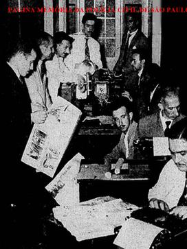 """Repórteres da Sala de Imprensa da Central de Polícia da Primeira Delegacia Auxiliar, no Páteo do Colégio, na década de 60. O primeiro com o jornal na mão, o Vieira """"Boca de Burro"""". O de terno cinza, escrevendo à máquina é o Antonio Soares, do Estadão, também conhecido como """"Verão Vermelho"""" e """"Nariz de Manchete""""."""