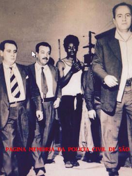 """Em 1.958, no bairro de Vila Ema, a prisão de Jorge Tavares, vulgo """"Jorginho"""" (de camiseta branca), braço direito do marginal Antônio Rossini, o """"Promessinha"""". À frente, o Investigador Carlos Augusto Scardovelli """"Paraguaio""""; de gravata listrada, o reporter Nelson Gato (participou da prisão) e ao seu lado Aduzindo Uribe """"Aduzindo Tiroteio"""". Acervo do advogado Dermeval Campos """"Campinho""""). Credito, foto da Folhapress."""