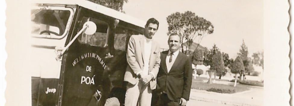 Viatura Jeep, em meados dos anos 60, em frente à Delegacia de Poá que ficava ao lado da Praça Rui Barbosa. Policial não identificado e a direita o Escrivão José Maia da Nobrega. (enviado por Neusa Maria Rambaldi).