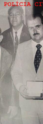 """Investigador Sócio Russo, recebendo o Título de Policial do ano, nas dependências da Secretaria de Segurança Pública, em 1.976. Escrivão Clovis Macedo; Delegado Dirienzo; Investigadores Gomes, """"Tidão"""", Capozzi, Sócio Russo (em primeiro plano, bigode e terno claro), Rubens Álfaro Sotto (presidente da Associação dos Funcionários da Polícia Civil) e Sr Paschoal Russo (Pai). Acervo de Ricardo D. Rosa, da página Tudo por São Paulo, 1932)"""