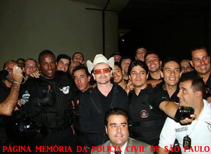 """O cantor e músico irlandês, vocalista principal da banda de rock irlandesa U2, Paul David Hewson, mais conhecido por seu nome artístico """"Bono Vox"""", sendo escoltado por policiais do GARRA e do DEIC F13 (Motocicletas), no Show realizado no Estadio do Morumbi/SP, em 10/04/2006. (Acervo do Escrivão Manuel Neto)."""