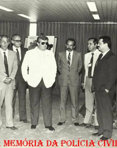 "Dependências do DETRAN, na década de 80. À partir da esquerda, (?), Delegados Camargo Lima, (?), Cyro Vidal Soares da Silva ""in memorian"", (?), (?), Senador Delegado Romeu Tuma e (?)."
