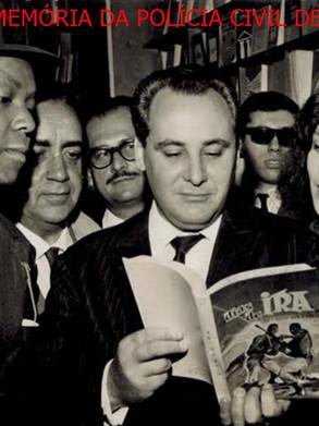 """Jornalista NELSON GATTO, de admirável sapiência, profissional dinâmico, entusiasta, trabalhador, poliglota, foi um dos maiores repórteres policiais do Brasil. Estudou na Faculdade de Direito de São Paulo no Largo de São Francisco.  Trabalhou nos jornais, """"A Noite de São Paulo""""; """"A Hora""""; """"Ultima Hora""""; """"Diário de São Paulo""""; """"Diário da Noite"""" onde foi diretor de jornalismo; revistas """"Edição Extra"""" e """"O Cruzeiro"""".  Foi correspondente de guerra dos Diários Associados em várias regiões onde ocorreram graves crises internas e conflitos mundiais, alcançando notoriedade.  Apresentou telejornais informativos nas redes das Emissoras Associadas, TV Cultura (Canal 2) e TV Tupi (Canal 4) de São Paulo.  No período de 1961 a 1964, ocupou a direção do Serviço de Repressão ao Contrabando da Polícia Federal no Estado de São Paulo.  Escritor deixou diversas obras literárias de expressão: Dias de Ira; O dia em que Goa Caiu; Navio Presídio; Assalto dos 500 Milhões, dentre outras. Faleceu em 1986, aos 58 anos de idade em São Paulo, deixando uma imensa lacuna no meio jornalístico.  Na foto, noite de autógrafos do lançamento do livro de sua autoria """"O Dia em que Goa Caiu"""", na Livraria Exposição do Livro, em 29/01/1965, vendo-se, o Investigador Chefe da RUDI Washington Gomes de Campos """"Campinho"""", o autor Nelson Gatto e a escritora Adelaide Carraro, célebre pelo livro """"Eu e o Governador"""". Acervo do advogado Dermeval Gomes Campos """"Campinho""""."""