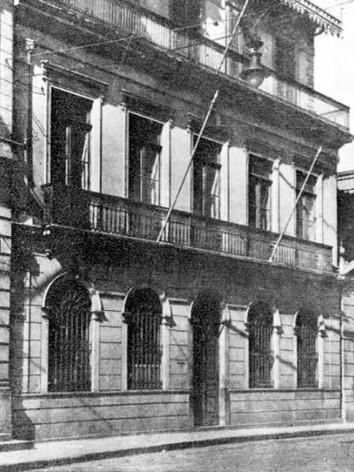 Casa Número Um, em fotografia de 1920.  Conhecida por situar-se à antiga rua do Carmo no 1 - atual rua Roberto Simonsen no 136-B, a Casa no 1 é um sobrado de três andares construído onde existiu até o ano de 1870 uma casa de taipa de pilão, no estilo bandeirista.  Seu primeiro proprietário, segundo registros de 1689, foi Francisco Dias. Após sua morte, o imóvel foi vendido a Gaspar de Godoy Moreira, cujos filhos e descendentes fizeram uso da casa como moradia. Em 1855 foi transformada no colégio Ateneu Paulistano e, após a morte de seu último diretor, foi vendida ao Major Benedito Antônio da Silva, responsável pela construção em alvenaria (1880), preservada até os dias de hoje. A nova construção aproveitou, provavelmente, a antiga estrutura das fundações de taipa de pilão. Sobre ela ergueram-se novas paredes em alvenaria de tijolos. Outros materiais utilizados em sua construção como o pinho-de-riga nas esquadrias, e a telha tipo francesa na cobertura, tornaram-se comuns nas construções paulistanas desse período.  Em 1890 funcionou como sede da Estação Central de Urbanos e da Sociedade de Imigração. Quatro anos mais tarde, o imóvel foi adquirido pelo Governo do Estado e passou a abrigar escritórios da Cia. de Gás até o ano de 1910. Em seguida, durante quatorze anos, a Casa abrigaria vários órgãos ligados à policia, como a Chefatura de Polícia, o Gabinete de Investigações e Capturas, o Gabinete Médico Legal e a Primeira Delegacia Auxiliar de Polícia. Até o ano de 1970, a Casa foi propriedade da Polícia tendo passado ao longo desse tempo, por várias reformas e reparos de urgência. Entre 1971 e 1974, já sob administração municipal, o imóvel foi utilizado por duas instituições culturais: o Instituto Genealógico Brasileiro e a Academia Paulista de Direito. Em 1976, foi elaborado pelos técnicos do Departamento do Patrimônio Histórico (DPH), um projeto de restauro que incluiu a decapagem de sucessivas camadas de pintura e a prospecção da alvenaria e forros, que possibilitar