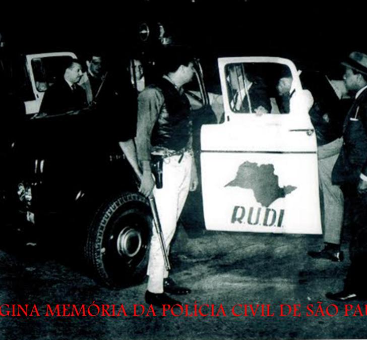 """Comemoração 60 anos da RUDI (1955-2015). RUDI - Rondas Unificadas do Departamento de Investigações. Grupo de elite da Polícia Civil de  São Paulo. Fundada no dia 15 de dezembro de 1955, pelo Delegado Paulo Silveira da Mota, diretor do DI- Departamento de Investigações (atual DEIC), teve como seu primeiro delegado titular, o Delegado Coriolano Nogueira Cobra. Na sua fase áurea foi comandada pelo Dr. José Carlos Baptista """"Zebú"""" e por Washington Gomes de Campos """"Campinho"""". Seus integrantes eram selecionados entre os melhores, de comprovada competência profissional, muito bem treinados. Páginas memoráveis de sua história foram escritas por policiais que patrulhavam a cidade  vestindo coletes de couro preto, portando armas automáticas, submetralhadoras e Winchester  44 """"Papo Amarelo"""".  A RUDI trabalhava nos moldes da """"Flying Squad"""", a esquadra de policiamento móvel da Polícia Metropolitana Inglesa, da Scotlan Yard, funcionando no período noturno, comportando um quadro de 80 homens divididos em três equipes, dirigidas cada qual por um delegado de polícia que permanecia no carro piloto. A RUDI foi um órgão memorável da Polícia de São Paulo, o mais famoso de seu tempo, com  tamanha intensidade, que seus feitos eram registrados diariamente no Jornal """"A Gazeta  Esportiva"""" em uma coluna denominada """"RUDI de Madrugada"""", escrita pelo repórter policial e Investigador Wilson Cocchi. Da mesma forma, o desenhista Mauricio de Sousa, editava a tira diária """"POLÍCIA FANTASMA"""", na Folha de São Paulo, descrevendo os feitos da RUDI. Também a Rádio Record tinha como atração diária o programa """"A Ronda da RUDI"""" produzido pelo radialista Fred Jorge.  A TV Cultura de São Paulo, Canal 2, apresentava uma vinheta da RUDI iniciando o programa  """"Um Fato em Foco"""" com o jornalista e criminalista Ney Gonçalves Dias. Na foto, tirada na Rua Brigadeiro Tobias, 527, em frente ao Departamento de Investigações de onde partiam as viaturas, aparecem da esquerda para a direita: Delegado de Equipe Waldemar Fragas"""