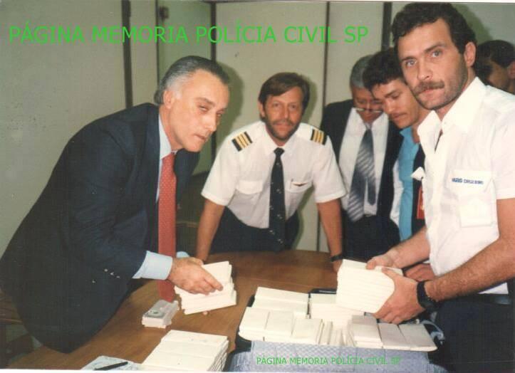 """Prisão de traficante colombiano que trazia, em duas malas, no aeroporto de Guarulhos, um milhão setecentos e cinquenta mil dólares falsificados, no final da década de 80. O uniforme de comandante usado pelo Delegado George H Millard, que era do tempo que foi piloto do SAT, foi perfeito para o trabalho. Na foto, à época, Delegado de Polícia Diretor do DEIC Claudio Gobbettt e Paulo Sérgio Fleury, da DISE Divisão de Investigações sobre Entorpecentes do DEIC, ao lado de camisa azul claro Investigador Arilton Ordones """"Biro Biro"""". De gravata azul ao fundo Delegado Penteado. e ao fundo Investigador Aronzo Zulio """"in memorian""""."""