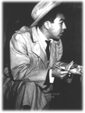 """Repórter Policial Maurício de Souza: Dick Tracy entrando na chefatura de polícia? Bem, o personagem usava capa de chuva e chapéu, como o detetive das tiras dos jornais americanos da década de 1930. Mas não era um detetive, era um repórter policial. Não estava nos States, mas na moderna São Paulo de 1957. A chefatura era na verdade a Central de Polícia, ao lado do Pátio do Colégio. A vestimenta do repórter ficava um tanto deslocada, mas ele não se importava. Seu nome: Maurício de Souza. Ficou um ano nessa vida. Depois seguiu seu destino de desenhista e inventou Bidu, Franjinha e toda a turma da Mônica.  Ele dizia que se fantasiava de detetive americano porque era tímido. Vestido como herói, tinha coragem para falar."""" . Além da timidez, Maurício de Souza tinha aquele outro sério problema. """"Era uma coisa horrível, eu não podia ver sangue que desmaiava"""". No local de um crime, pedia socorro ao fotógrafo. """"Ele olhava o corpo e me dizia como estava, se era em decúbito ventral (barriga para baixo)"""" - conta, divertindo-se com o linguajar técnico. Cama de casal – Maurício trabalhava de madrugada. Naquelas em que nada acontecia, e como não aderisse ao jogo, juntava as mesas (podia ser a da Folha, onde trabalhava, a dos Diários, a da Última Hora, do Estadão), e assim tinha uma cama """"grande como de casal"""". Fazia um travesseiro de jornais amassados, deitava-se e dormia... É verdade que, em plena madrugada, podia ser incomodado por uma notícia. Neste caso, pedia condução e fotógrafo, e a Folha da Manhã (hoje Folha de S. Paulo) mandava o carro da reportagem, um jipe laranja. Podia chegar também o jipe dos Diários Associados (que Bussab, em outras horas, também usava). Naquela época, a periferia da cidade não era asfaltada. Muitas vezes Maurício se deparava com um crime passional, o marido pegou a mulher com o amante, ou vice-versa. """"Na confusão, a família chorando, eu cumpria ordens do jornal: roubava a foto do casamento."""" Era ótima ilustração para a reportagem. Maurício achava """"um"""