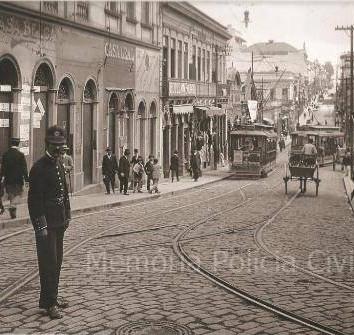 Guarda organizando o trânsito, em primeiro plano, na Rua de São João em 1908, vista da esquina com a Líbero Badaró, em direção ao Mercadinho do Acu, (plano médio, à direita). Ao fundo, à esquerda, a lateral do Conservatório Dramático e Musical. Em frente ao Mercadinho, o Bijou Theatre, prédio em lugar do qual foi construída a Delegacia Fiscal. À esquerda, lacrado para demolição, o sobrado da Casa Belga, de armas e munições; a seguir, a Casa Leal e o Hotel Bologna.