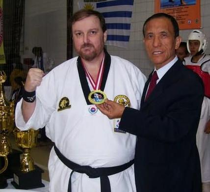 O Grão-mestre Dr. Hong Soon Kang, faixa preta 10º Dan, entrega a medalha de ouro em KIOK-PA (quebramentos) ao Policial Civil João Caçula Kasemiro da Seccional de São Sebastião, no Campeonato Mundial de Tae Kwon Do e Hapkido 2012.
