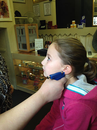 Image of a girl having her ears pierced at our jewellery shop in Ramsey cambridgeshire