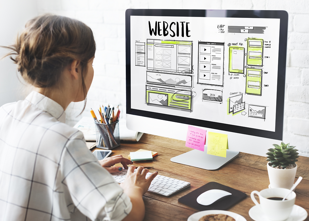 Lady looking at a desktop with a website design and layout