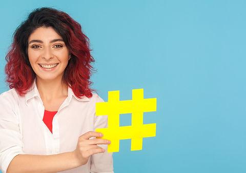 Social Media. Professional woman holding a Hash Tag Symbol.