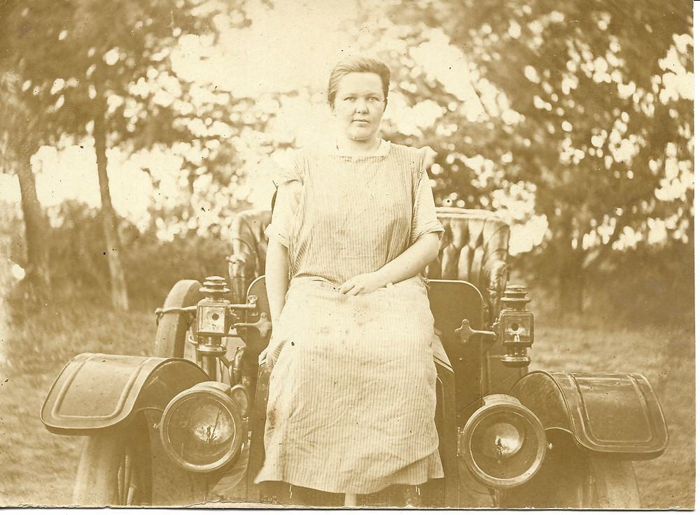 My great grandmother perched upon the hood of her car.