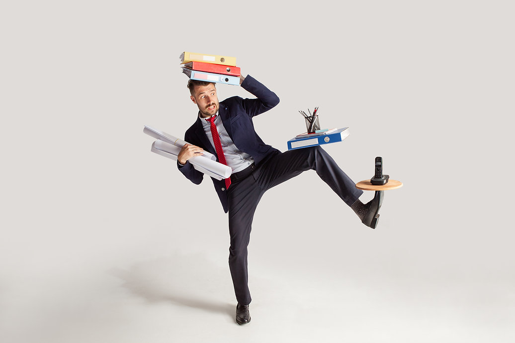 Young businessman in a suit juggling with office supplies in his office, isolated on white