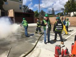 CERT student using fire extinguisher